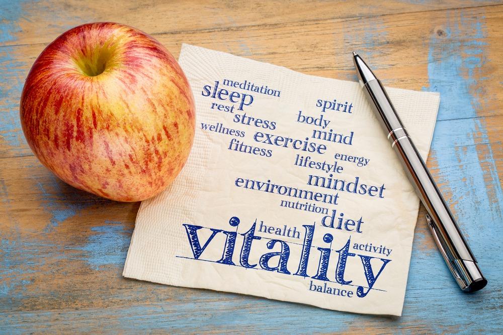 Apfel auf einem Tisch, daneben liegt ein Zettel auf dem Wörter wie Vitality geschrieben sind.