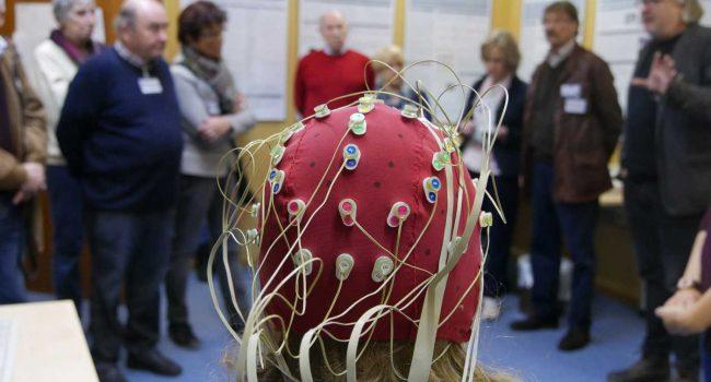 Probandin mit EEG-Kappe vor Besucherinnen und Besuchern.