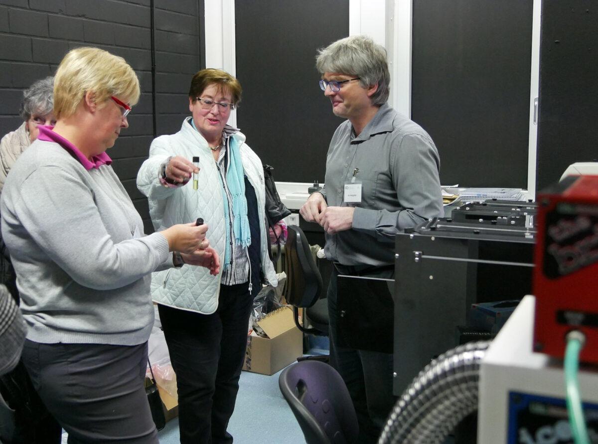 Prof. Jan Hengstler mit Besuchern vor dem Mikroskop